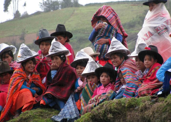 11Local women and children protect themselves from the rain by putting a plastic bag on their hats and colorful ponchos around their shoulders. Community-based tourism in Peru - RESPONSible Travel Peru