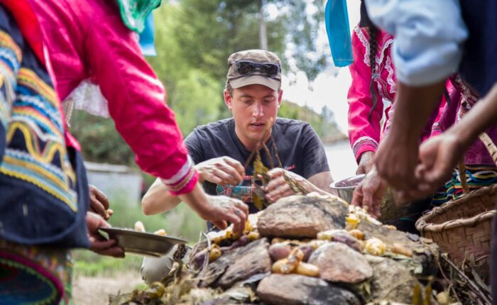 Guido assisting the locals in Vicos with opening the Pachamanca and gathering the freshly cooked potatoes. Community-Based Tourism in the Andes - RESPONSible Travel Peru