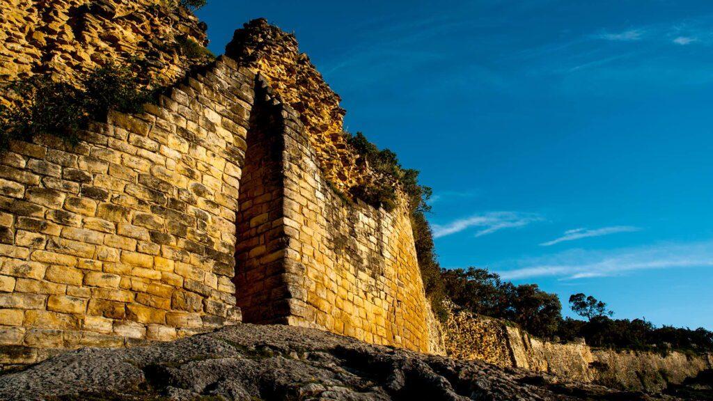 Kuelap's slim entrance in a yellowish rock wall that seems to be infinite along the mountain ridge | Responsible Travel Peru