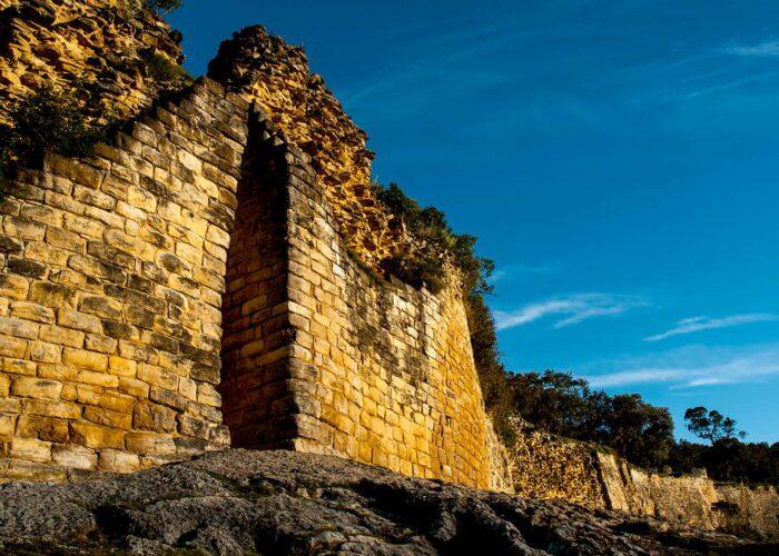 Kuelap's slim entrance in a yellowish rock wall that seems to be infinite along the mountain ridge   Responsible Travel Peru
