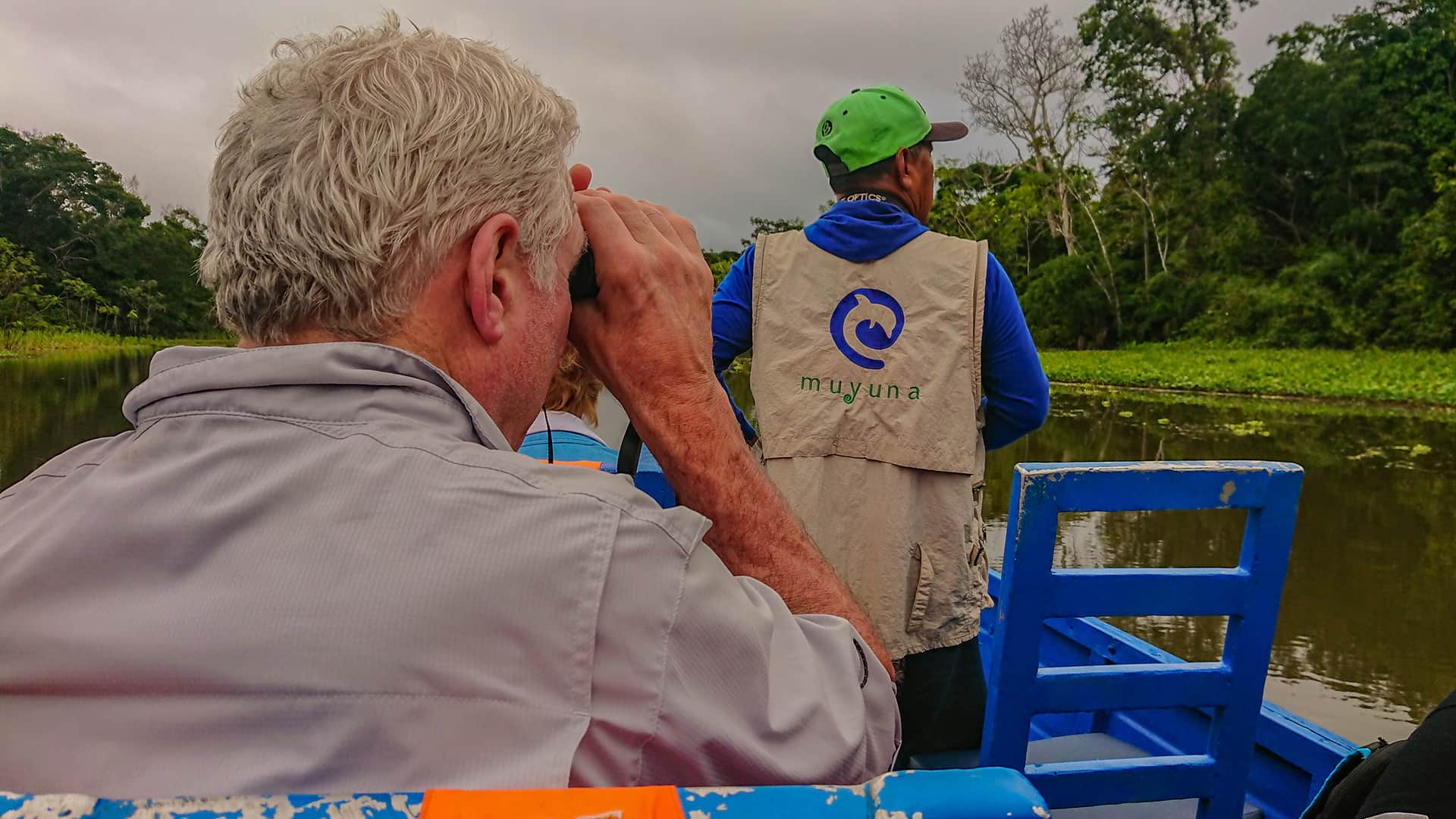 11Man with binoculars behind guide on a river boat | Responsible Travel Peru