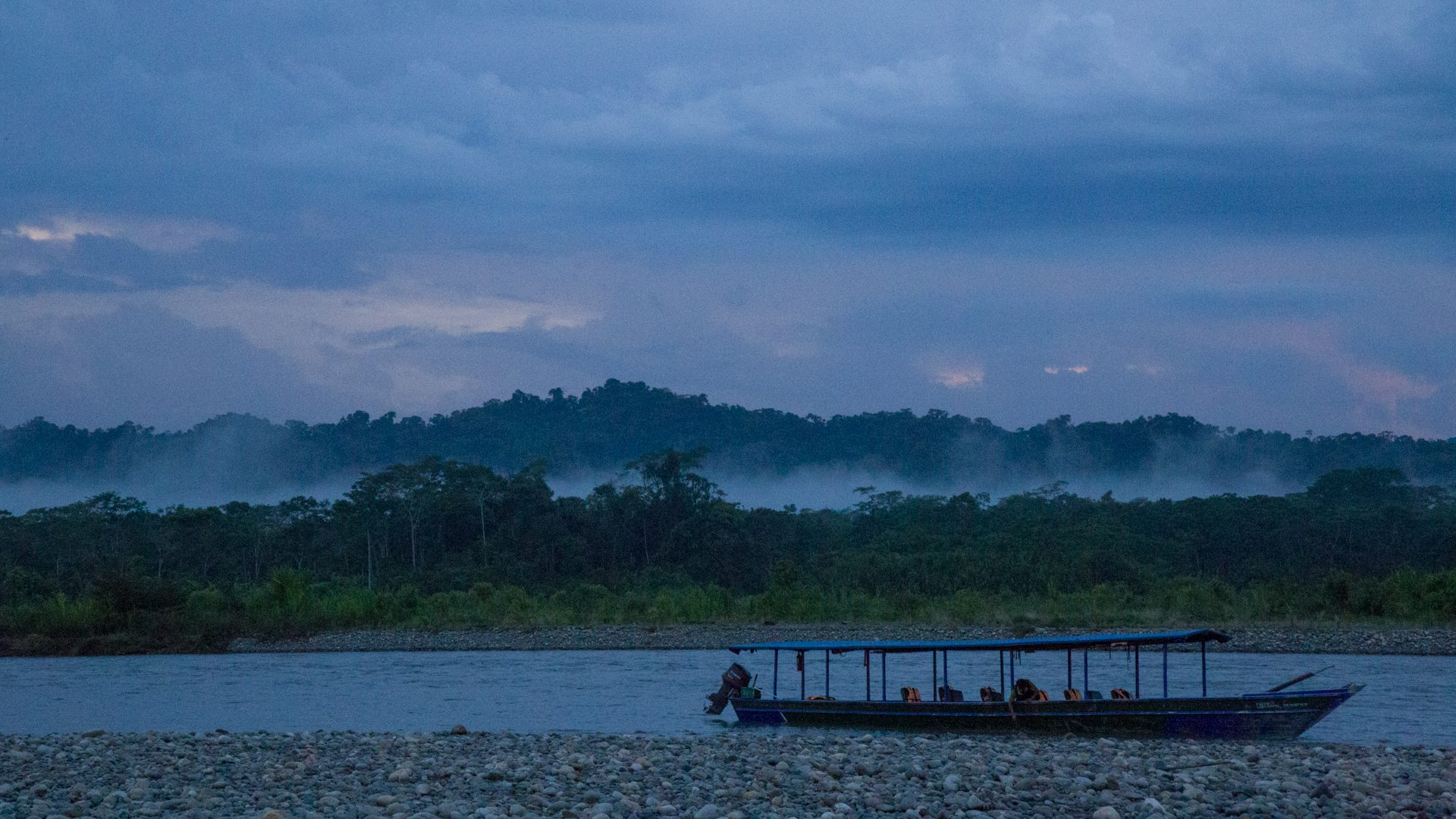 11Stationed boat with a background of foggy forest and clouded sky | Responsible Travel Peru