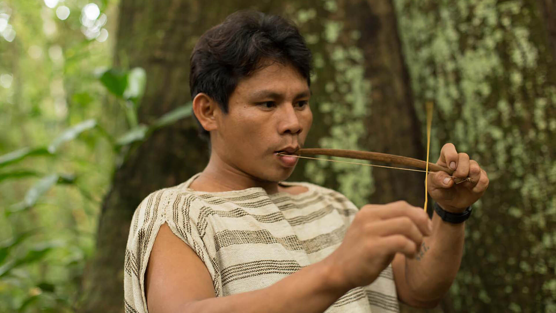 11Matsigenka young man playing mouth violin in Manu | Responsible Travel Peru