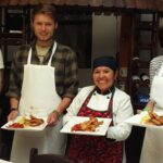 Selia and three young travelers showing off the dishes after the cooking class | Responsible Travel Peru