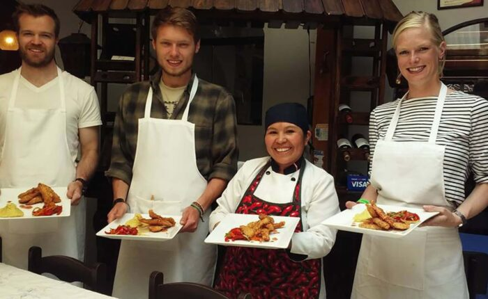 Selia and three young travelers showing off the dishes after the cooking class   Responsible Travel Peru